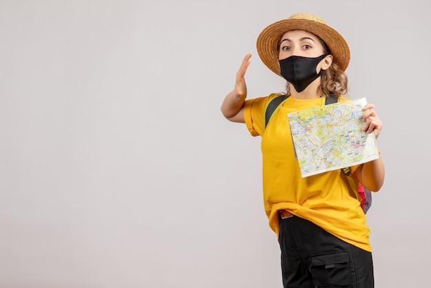 Vooraanzicht van schattige vrouwelijke reiziger met de kaart van de rugzakholding op witte muur