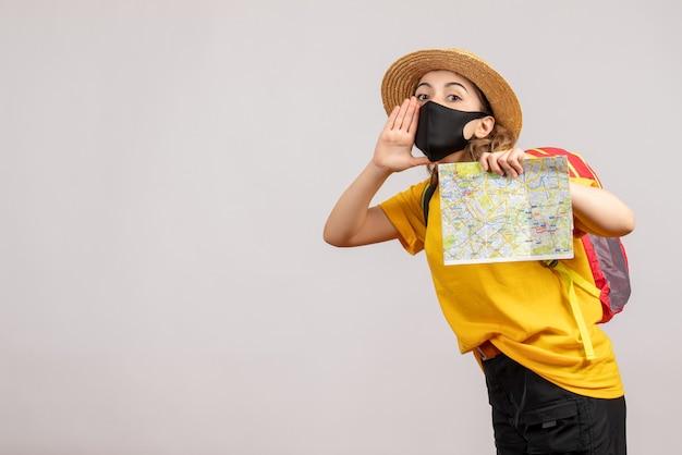 Vooraanzicht van schattige vrouwelijke reiziger met de zwarte kaart van de maskerholding op witte muur