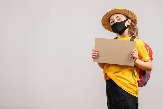 Vooraanzicht van schattige vrouwelijke reiziger met het karton van de rugzakholding op grijze muur