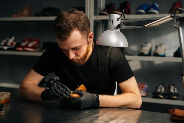 Vooraanzicht van schoenmaker die zwarte latexhandschoenen draagt die oude lichtbruine leerschoenen wrijf...