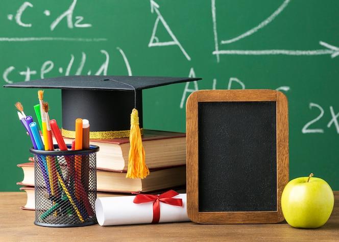 Vooraanzicht van schoolbord met academische pet en potloden