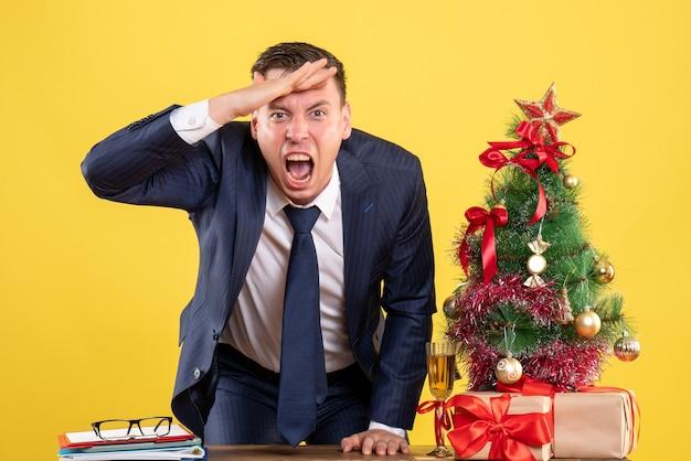 Vooraanzicht van schreeuwende man die hand op haar voorhoofd in de buurt van de kerstboom en presenteert op geel