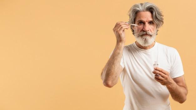 Vooraanzicht van senior bebaarde man serum toe te passen