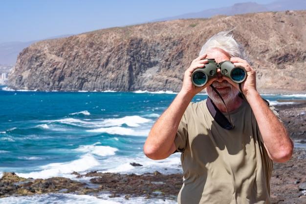 Vooraanzicht van senior man met verrekijker kijken lachend naar de camera. senior witharige gepensioneerde m/v genieten van pensioen op zee. kliffen en bergen op de achtergrond