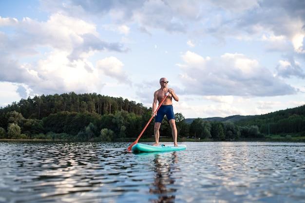 Vooraanzicht van senior man paddleboarding op meer in de zomer. ruimte kopiëren.