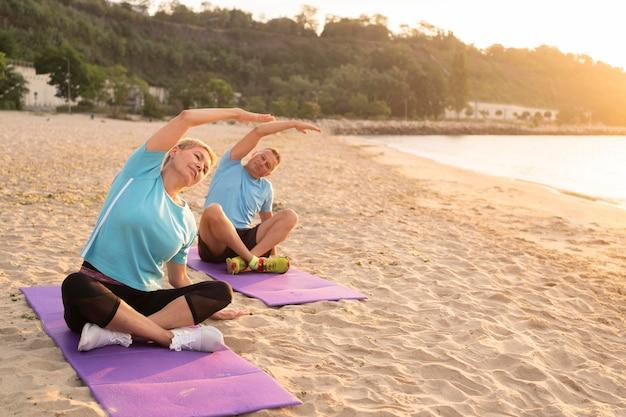 Vooraanzicht van senior paar die zich uitstrekt op het strand