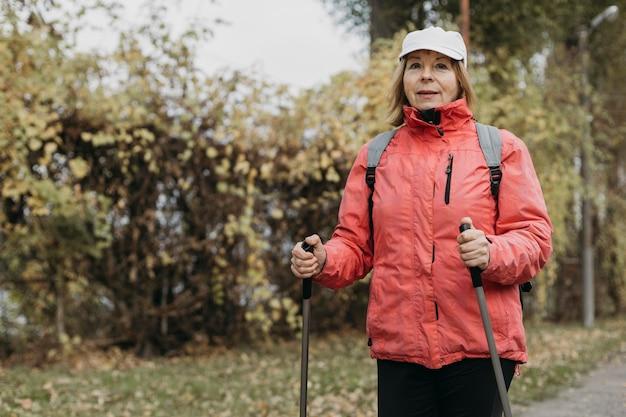 Vooraanzicht van senior vrouw buiten wandelen met kopie ruimte
