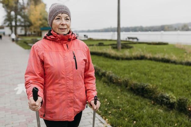 Vooraanzicht van senior vrouw buitenshuis met wandelstokken en kopieer de ruimte