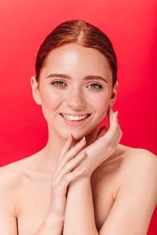 Vooraanzicht van sensueel kaukasisch meisje met leuke glimlach. studio shot van verfijnde naakte vrouw geïsoleerd op een rode achtergrond.