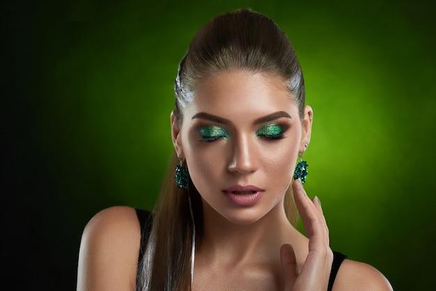 Vooraanzicht van sensuele brunette meisje met glanzende groene make-up aan te raken perfecte bronzen huid van het gezicht. mooie vrouw met gesloten ogen, gekleed in zwarte top, grote ronde oorbellen verleidelijk poseren.