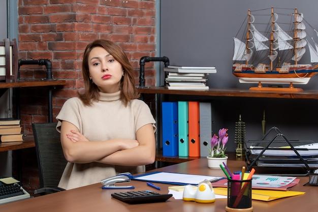 Vooraanzicht van serieuze mooie vrouw die handen kruist die op kantoor werken