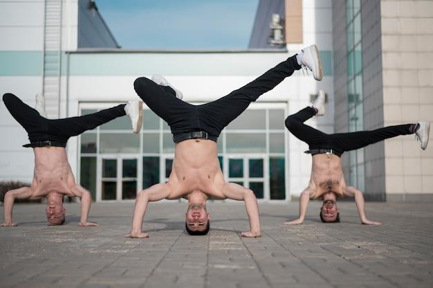 Vooraanzicht van shirtless hiphopartiesten die op hun hoofd dansen