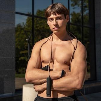 Vooraanzicht van shirtless man met springtouw buitenshuis