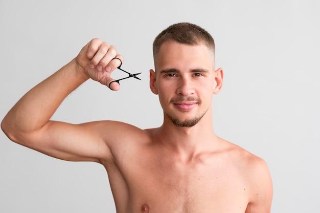 Vooraanzicht van shirtless man met vingernagels schaar