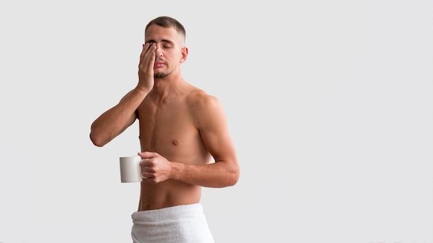 Vooraanzicht van shirtless slaperige man in de ochtend met koffie