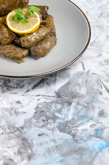 Vooraanzicht van smakelijke blad dolma binnen plaat op wit oppervlak