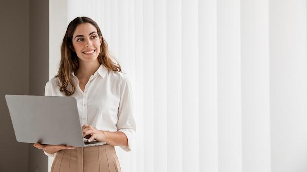 Vooraanzicht van smiley elegante onderneemster die laptop met exemplaarruimte met behulp van