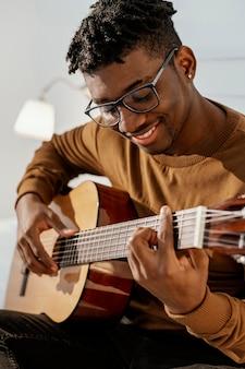 Vooraanzicht van smiley mannelijke musicus die thuis gitaar op bed speelt