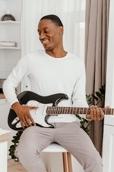 Vooraanzicht van smiley mannelijke musicus elektrische gitaar spelen