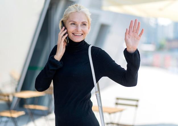 Vooraanzicht van smiley oudere vrouw buitenshuis op een telefoontje en zwaaien
