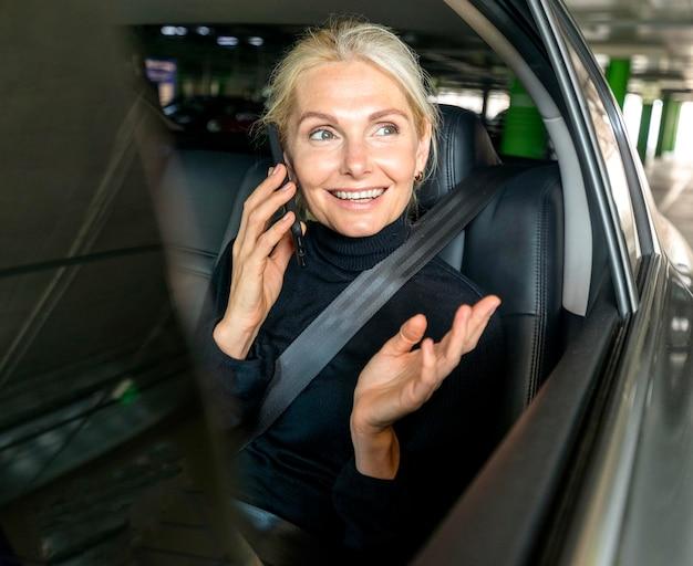 Vooraanzicht van smiley oudere zakenvrouw praten aan de telefoon in auto