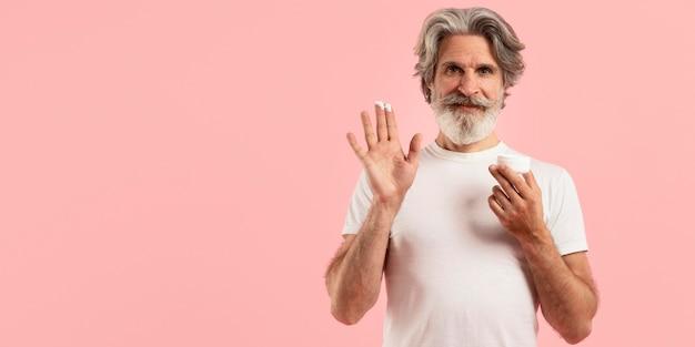 Vooraanzicht van smiley senior man met baard met crème