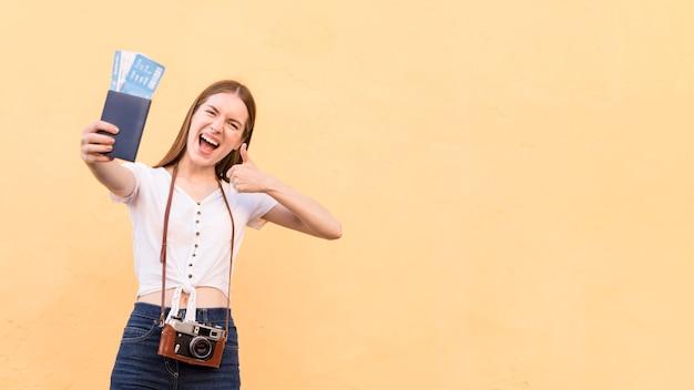 Vooraanzicht van smiley toeristische vrouw met paspoort en camera