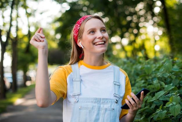 Vooraanzicht van smiley vrouw buitenshuis met smartphone
