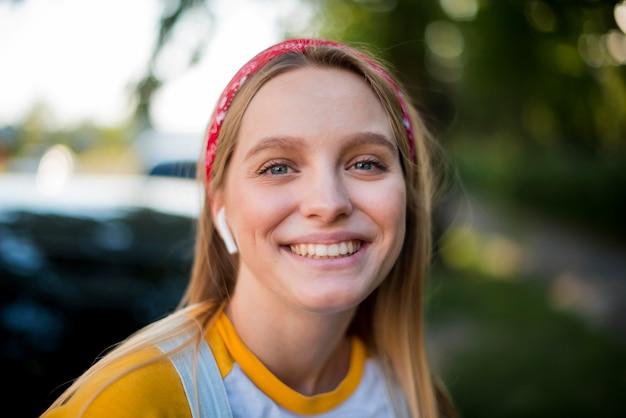Vooraanzicht van smiley vrouw met oordopjes