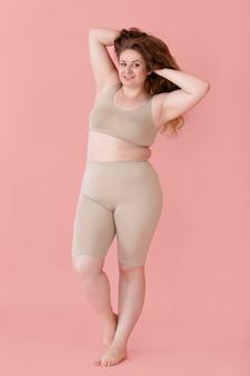 Vooraanzicht van smiley vrouw poseren terwijl het dragen van een body shaper