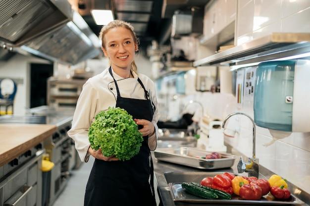 Vooraanzicht van smiley vrouwelijke chef-kok in de salade van de keukenholding