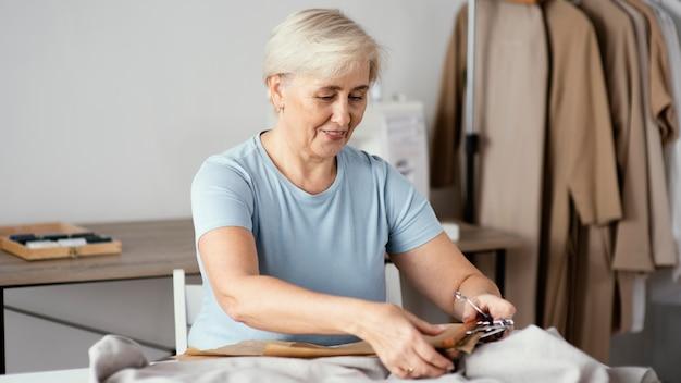 Vooraanzicht van smiley vrouwelijke kleermaker in de studio snijden stof