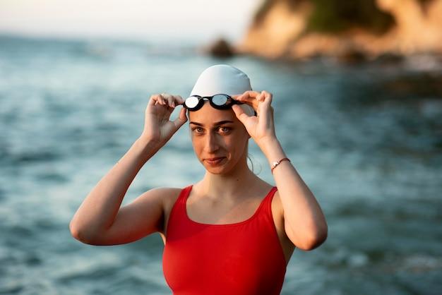 Vooraanzicht van smiley zwemster met bril en pet