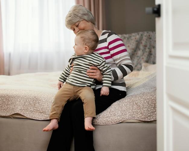 Vooraanzicht van smileygrootmoeder die haar kleinzoon houdt