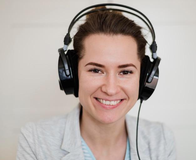 Vooraanzicht van smileyleraar die hoofdtelefoons voor online klasse draagt