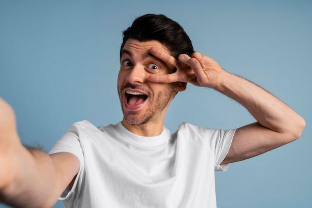 Vooraanzicht van smileymens die een selfie neemt en vredesteken maakt
