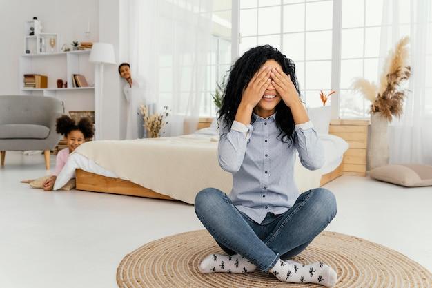 Vooraanzicht van smileymoeder die thuis verstoppertje speelt met haar kinderen
