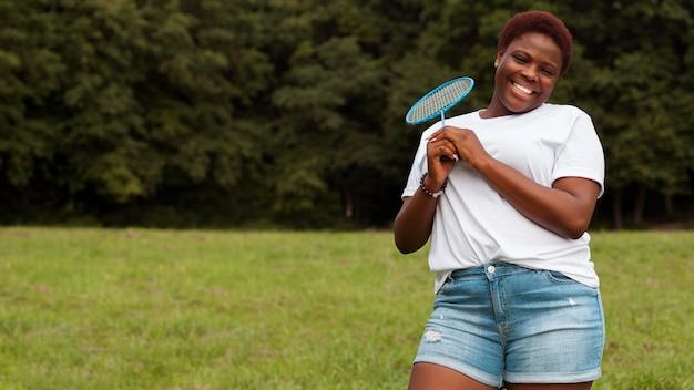 Vooraanzicht van smileyvrouw buitenshuis met racket