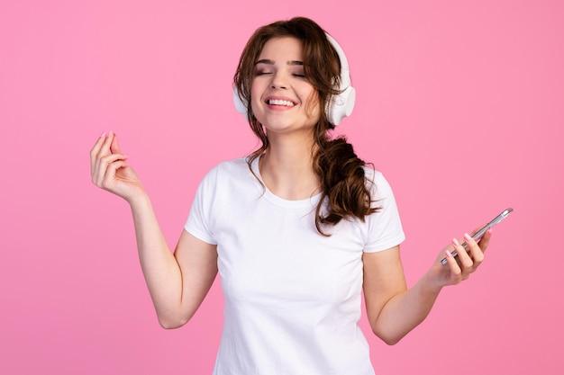 Vooraanzicht van smileyvrouw die aan muziek op hoofdtelefoons luistert