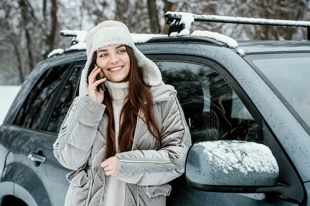 Vooraanzicht van smileyvrouw die de telefoon overneemt tijdens een roadtrip