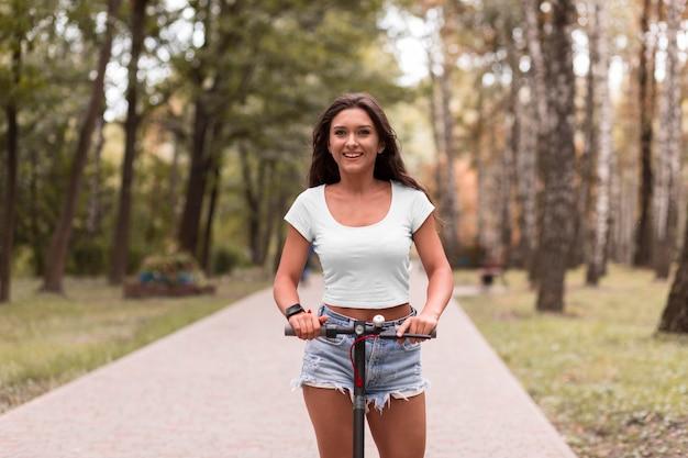 Vooraanzicht van smileyvrouw die een elektrische autoped berijdt