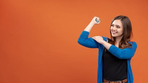 Vooraanzicht van smileyvrouw die haar biceps toont