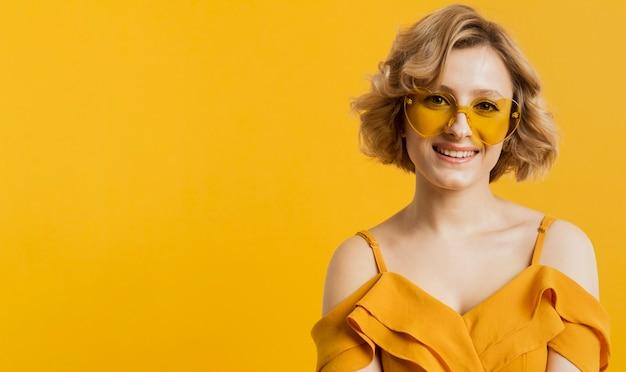Vooraanzicht van smileyvrouw die terwijl het dragen van zonnebril in evenwicht houdt