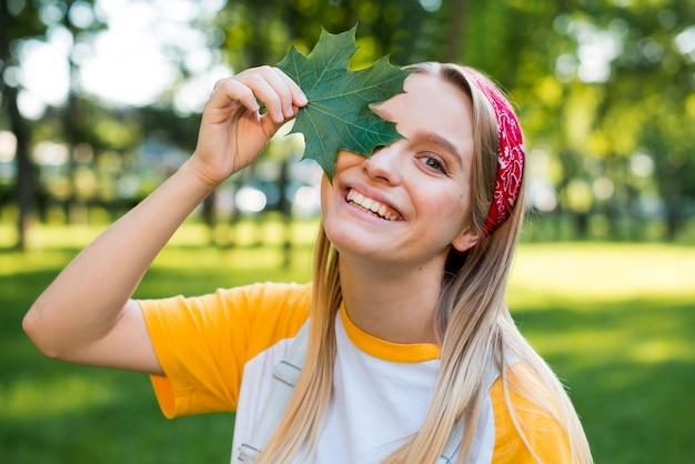 Vooraanzicht van smileyvrouw het stellen met blad