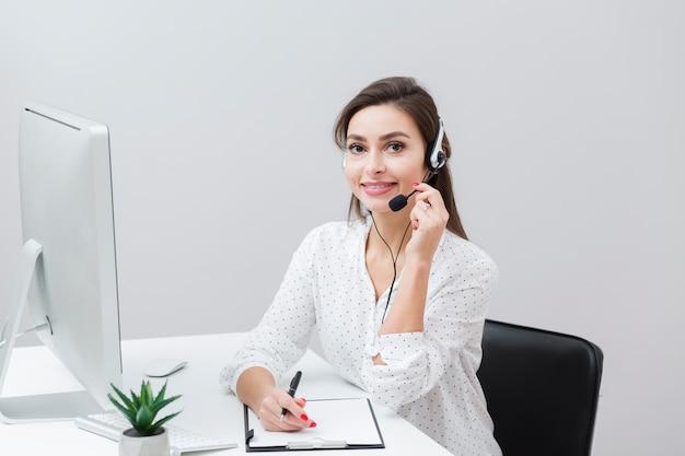 Vooraanzicht van smileyvrouw het stellen met hoofdtelefoon bij bureau