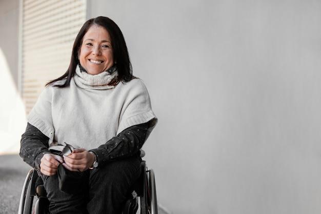 Vooraanzicht van smileyvrouw in een rolstoel met exemplaarruimte
