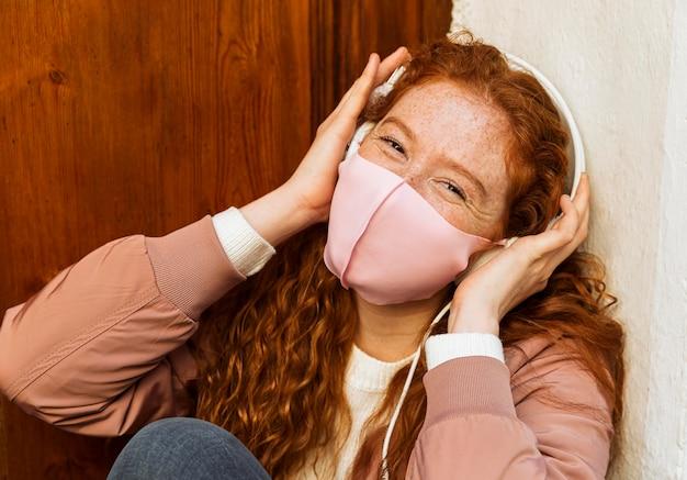 Vooraanzicht van smileyvrouw met gezichtsmasker in openlucht en hoofdtelefoons