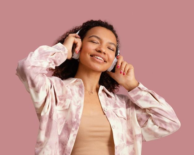Vooraanzicht van smileyvrouw met hoofdtelefoons die aan muziek luisteren