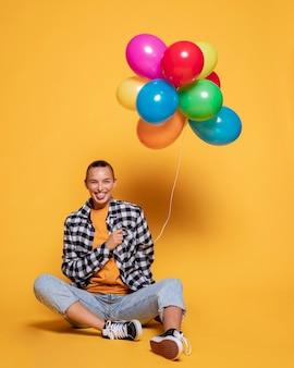 Vooraanzicht van smileyvrouw met kleurrijke ballons
