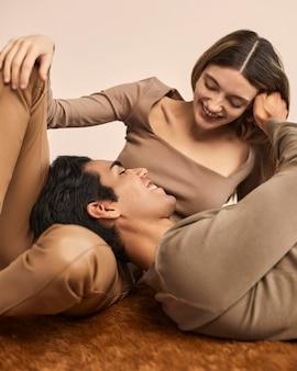 Vooraanzicht van smileyvrouw met man die zijn hoofd op haar schoot rust